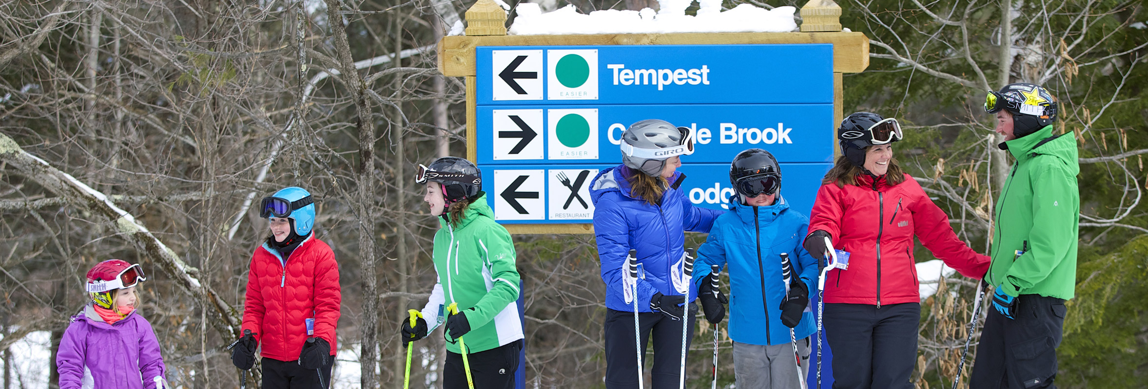 Photo of Skiers in front of trail signs